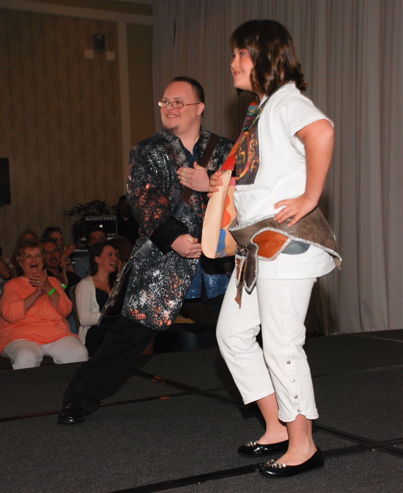 A male model waering jacket and posing in martial arts stance and female model with handbag across waist