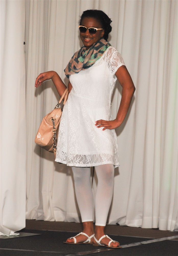 A female model wearing white dress, multi-colored scarf, white tights, sunglasses, and white sandals, posing with left hand on hip and right arm out holding blush color large handbag