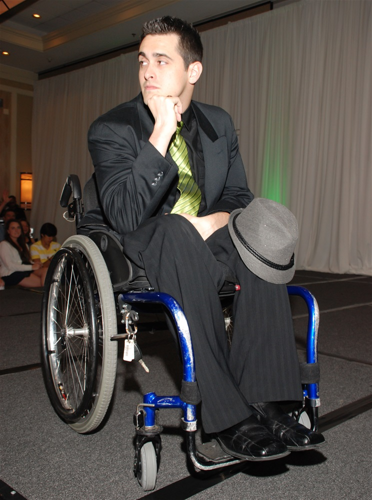 A male model in a wheelchair wearing black suit with light green tie and gray Fidora hat and chin resting on hand