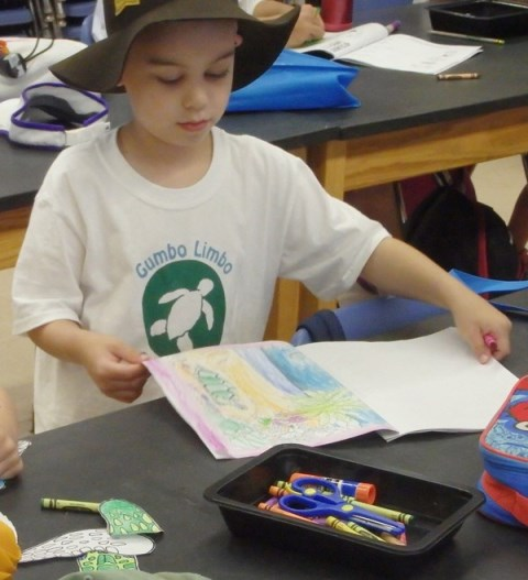Littl boy coloring in his sea turtle camp journal