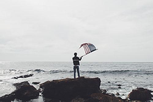 man on rocks at beach waving flag