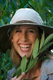 smiling woman holding tree branch wearing a hat