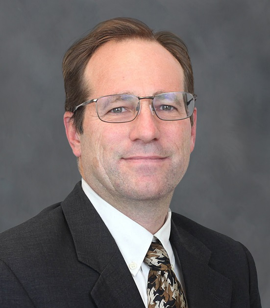 headshot of a man wearing glasses and a suit