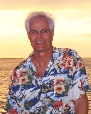 man wearing a tropical shirt with a sunset in the background